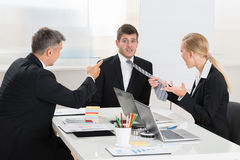 Two Businesspeople Quarreling To Young Businessman Royalty Free Stock Photo