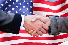 Two businesspeople shaking hands. Close-up Of Two Businesspeople Shaking Hands In Front Of American Flag royalty free stock image