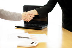 Two Businesspeople shaking hands indoors Royalty Free Stock Images