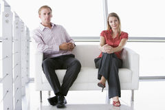 Two businesspeople sitting in office lobby smiling. Lookin at the camera stock images
