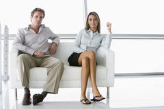 Two businesspeople sitting in office lobby smiling stock images