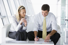 Two businesspeople sitting in office lobby talking. And smiling Stock Image