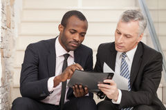Two businesspeople sitting on stairs and looking at papers. Stock Photography