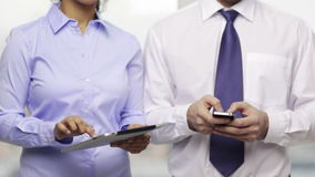 Two businesspeople with smartphone and tablet pc. Business, technology, internet and office concept - businessman and businesswoman with smartphone and tablet pc stock video footage