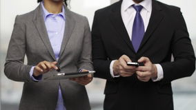 Two businesspeople with smartphone and tablet pc. Business, technology, internet and office concept - businessman and businesswoman with smartphone and tablet pc stock footage