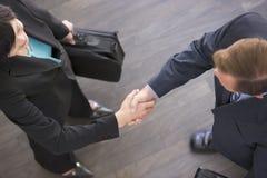 Two businesspeople standing indoors shaking hands. Two business people standing indoors chaking hands Stock Image