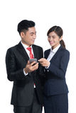 Two businesspeople standing using smart mobile phone Stock Images
