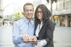 Two businesspeople on street with tablet computer Stock Images