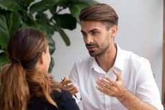 Two businesspeople talking focus on excited brainstorming caucasian employee. Man telling ideas female teammate sharing information experience. HR manager royalty free stock photos