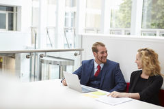 Two Businesspeople Using Laptop At Desk In Modern Office stock images