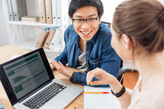 Two businesspeople using laptop and working together Stock Image