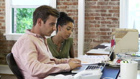 Two Businesspeople Working In Design Studio Together. Two businesspeople working at desks in modern office - female hands male document for her to read.Shot on stock footage