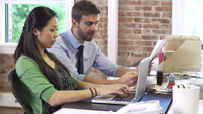 Two Businesspeople Working In Design Studio Together. Two businesspeople working at desks in modern office - male hands female document for her to read.Shot on stock footage