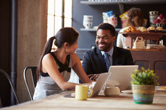 Two Businesspeople Working At Laptop In cafe stock photography