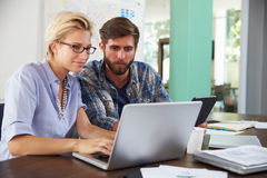 Two Businesspeople Working On Laptop In Office Together Royalty Free Stock Images