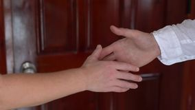 Two businessperson shaking hands; only hands to be seen and a key is be given. Two businessperson shaking hands only hands to be seen and a key is be given stock video