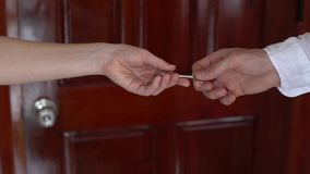 Two businessperson shaking hands; only hands to be seen and a key is be given. Two businessperson shaking hands only hands to be seen and a key is be given stock video footage