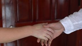 Two businessperson shaking hands; only hands to be seen and a key is be given. Two businessperson shaking hands only hands to be seen and a key is be given stock footage