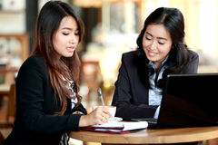 Two businesswoman is discussing important figures over their cof Stock Photography