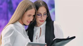 Two businesswoman discussing new project standing in modern laboratory using tablet