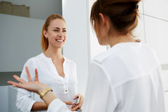 Two businesswoman dressed in formal wear laughing at funny incident on work while standing in modern office interior, Stock Photo