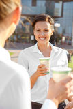 Two businesswoman having a coffee break. Two attractive businesswoman having a coffeebreak outdoors Stock Photo