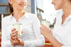 Two businesswoman having a coffee break. Two attractive businesswoman talking during coffeebreak outdoors Royalty Free Stock Photo