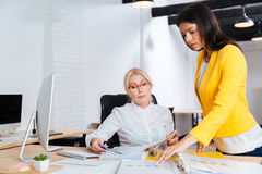 Two businesswoman having a meeting in the office. Two young and mature businesswoman having a meeting in the office Stock Image