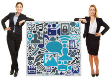Two businesswoman leaning on sign with social media icons Stock Photography