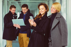 Two businesswoman looking smart phone in lobby with colleagues at background Stock Images