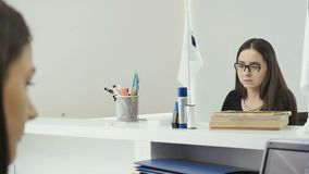 Two businesswoman sits at the office in front of each other and talking. Young woman lawyer in glasses and in black dress sits at the table in the white office stock video footage