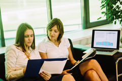 Two businesswoman sitting in the business center and discuss ideas Stock Photography