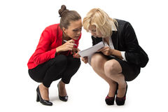 Two businesswoman sitting with sheet of paper Stock Photo