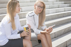 Two businesswoman talking. Couple of young beautiful businesswoman talking outdoor. Outdoor photo. Sunny day Stock Photos