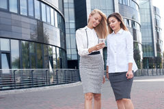 Two businesswoman talking. Couple of young beautiful businesswoman talking outdoor. Outdoor photo. Sunny day. Office building on background Royalty Free Stock Photos