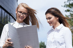 Two businesswoman talking. Couple of young beautiful businesswoman talking outdoor. Outdoor photo. Sunny day. Office building on background Stock Photo