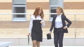 Two businesswoman walking on the street near office building stock video