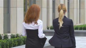 Two businesswoman walking on the street near office building, slow motion stock footage