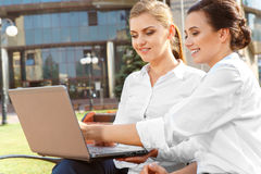 Two businesswoman working on laptop Stock Photos