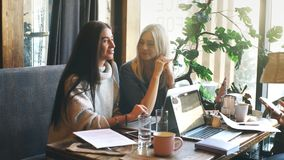 Two businesswoman working together about documents, partner discuss plan or idea and opinion meeting. Bussiness are discussing their working on a wood table stock footage