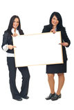 Two businesswomen with blank placard royalty free stock photography