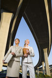 Two businesswomen with briefcase and folder beneath overpasses, low angle view Royalty Free Stock Photography