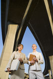 Two businesswomen with briefcase and folder beneath overpasses, low angle view Royalty Free Stock Photo