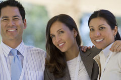 Two businesswomen and businessman standing with arms around each other, smiling Stock Photography