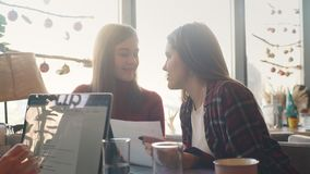Two businesswomen in a cafe discussing contracts and documents at lunch. Two businesswoman working together about documents, partner discuss plan or idea and stock video footage