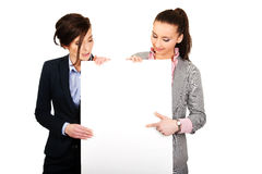 Two businesswomen carrying a big white board. Stock Images