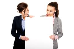 Two businesswomen carrying a big white board. Stock Photos