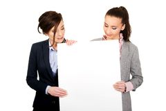 Two businesswomen carrying a big white board. Stock Image