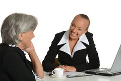 Two businesswomen with coffee and laptop Royalty Free Stock Images