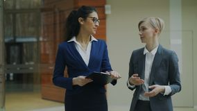 Two businesswomen colleagues discussing project while walking in modern office. Indoors stock footage